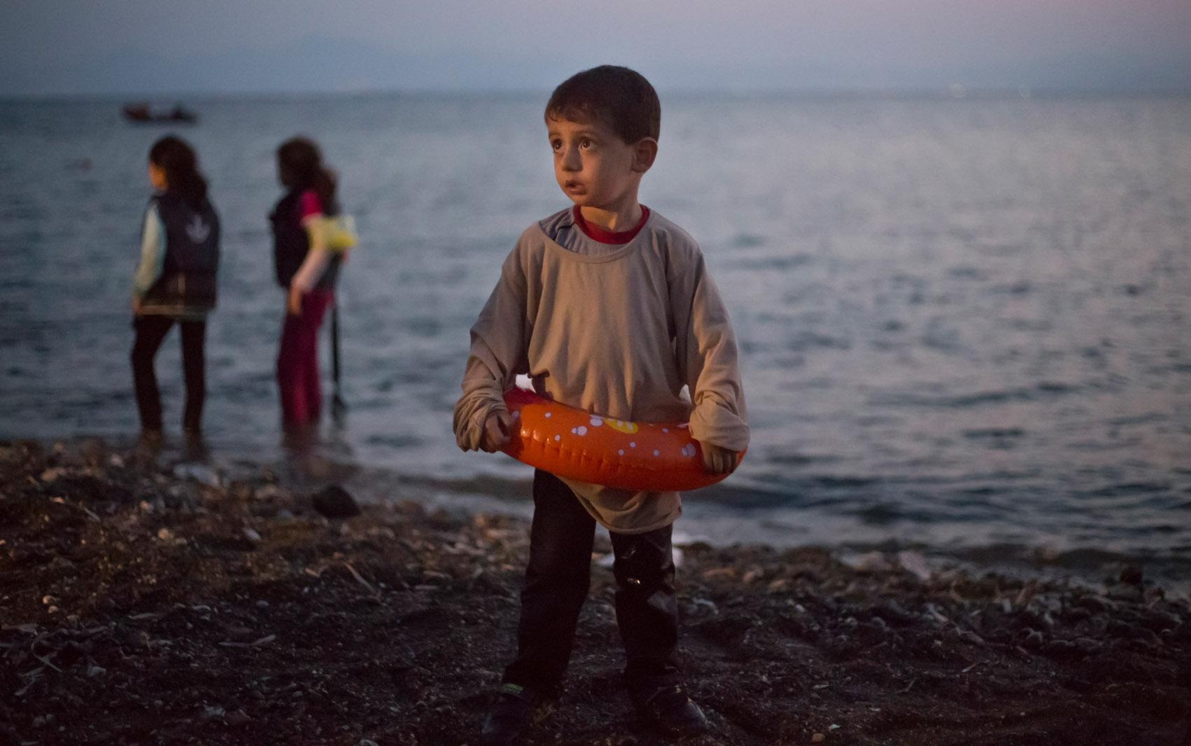 Menino imigrante sírio é visto ainda com uma bóia após chegada de bote na ilha grega de Kos