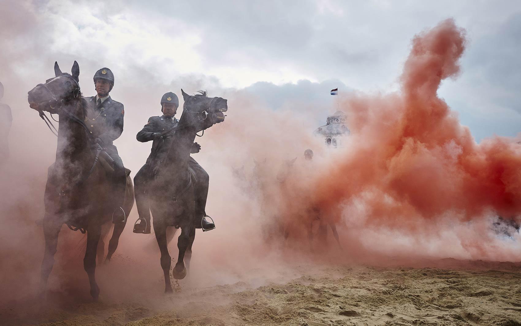 14/9 - Policiais passam cavalgando em meio a fumaça e bombas de efeito moral durante treinamento da cavalaria holandesa em Scheveningen. Cerca de 80 cavalos e policiais montados participam do treinamento a dois dias da cerimônia de abertura do Parlamento