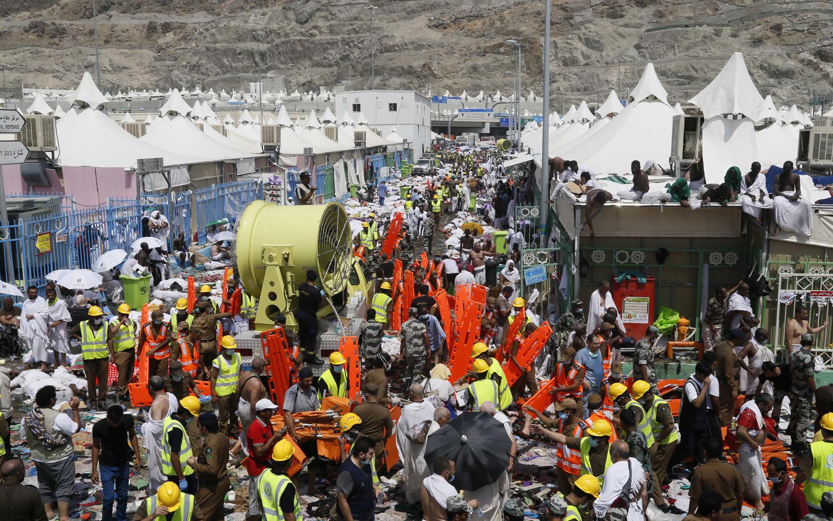 Peregrinos muçulmanos e equipes de resgate são fotografados ao lado das vítimas do tumulto que deixou centenas de mortos em Meca, nesta quinta-feira (24)