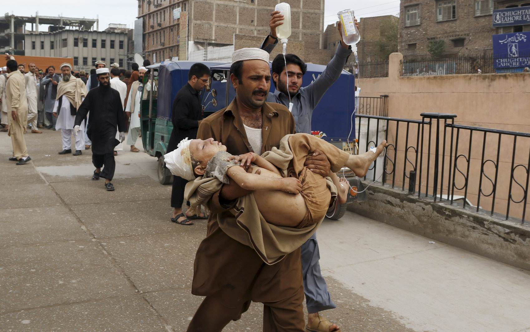 Um homem carrega um menino ferido até o hospital Lady Reading em Peshwar, no Paquistão, após forte terremoto na região