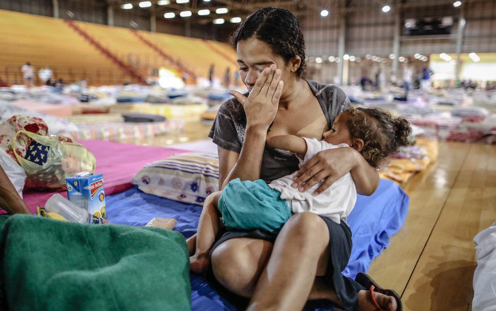 Uma mulher que ficou desabrigada após o rompimento de uma barragem de rejeitos da mineradora Samarco é vista com uma criança em um abrigo em Mariana, no interior de Minas Gerais