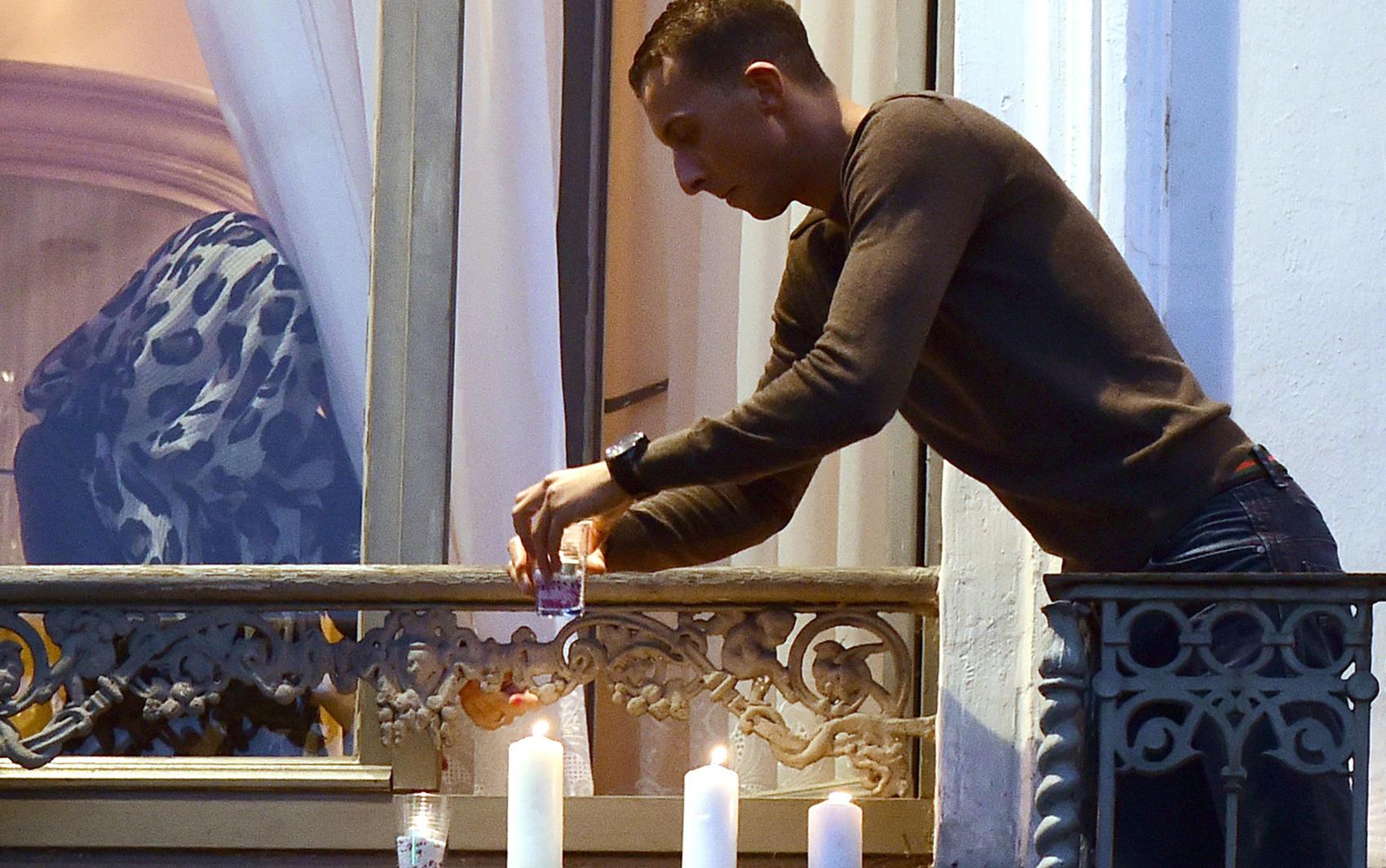 Mohamed Abdeslam, irmão de um dos homens que participou dos ataques terroristas em Paris, acende velas na sacada do apartamento de sua família durante uma vigília no distrito de Molenbeek, em Bruxelas, na quarta (18)