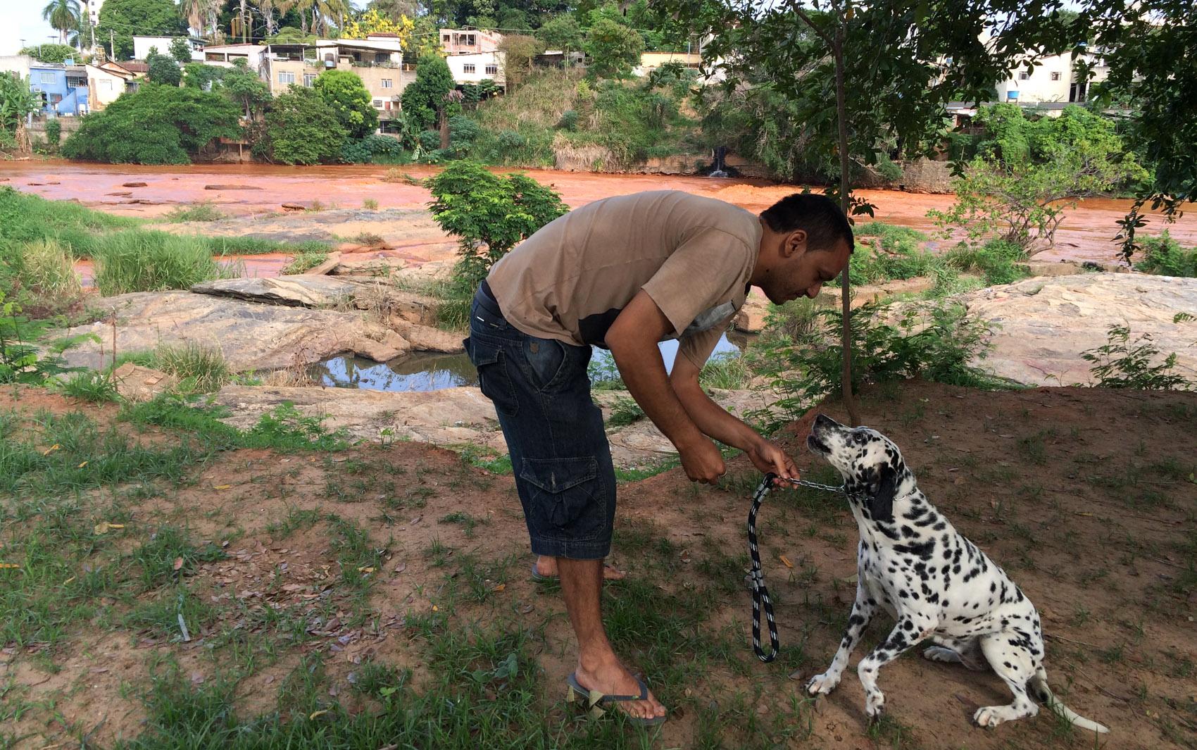 29/11 - André Luis Gonçalves é visto com a cadela Nina próximo à margem do Rio Doce em Governador Valadares, no interior de Minas Gerais. Nina costumava tomar banho todos os dias no rio, rotina interrompida após chegada da lama