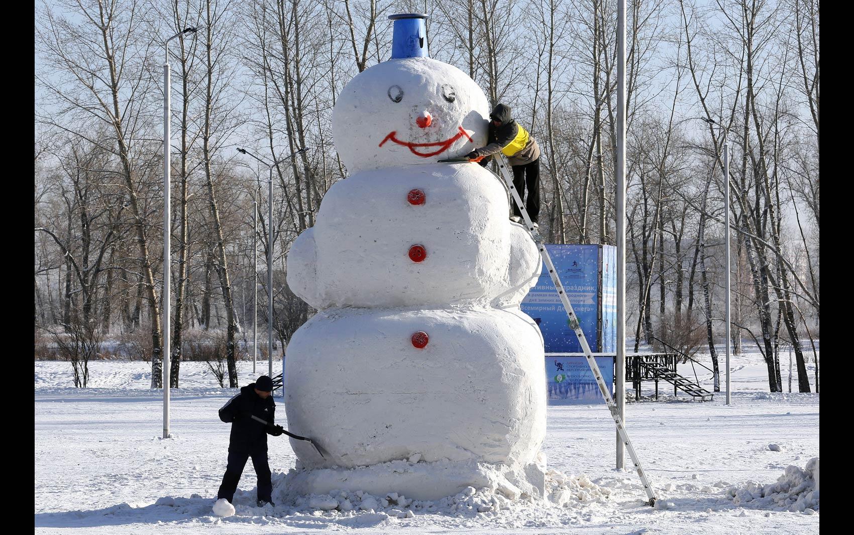 Dupla dá últimos retoques em um boneco de neve gigante com aproximadamente 5 metros de altura feito em um parque de Krasnoyarsk, na região da Sibéria, na Rússia