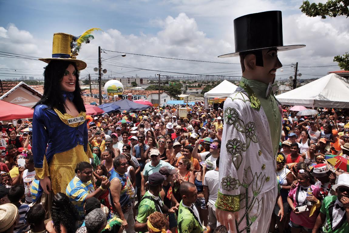 Homem da Meia-Noite e Mulher do Dia se encontram no desfile de bonecos gigantes