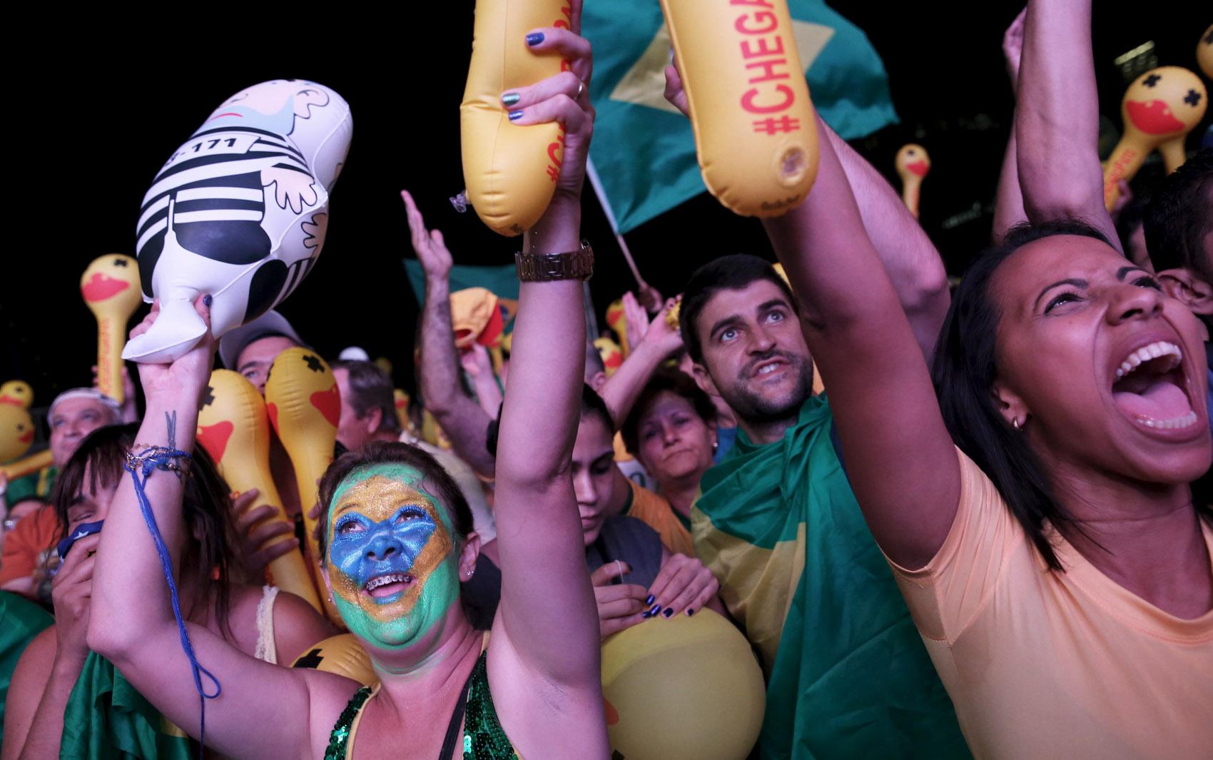 Manifestantes pró-impeachment comemoram enquanto assistem a votação do processo de impeachment em um telão instalado na Avenida Paulista, em São Paulo