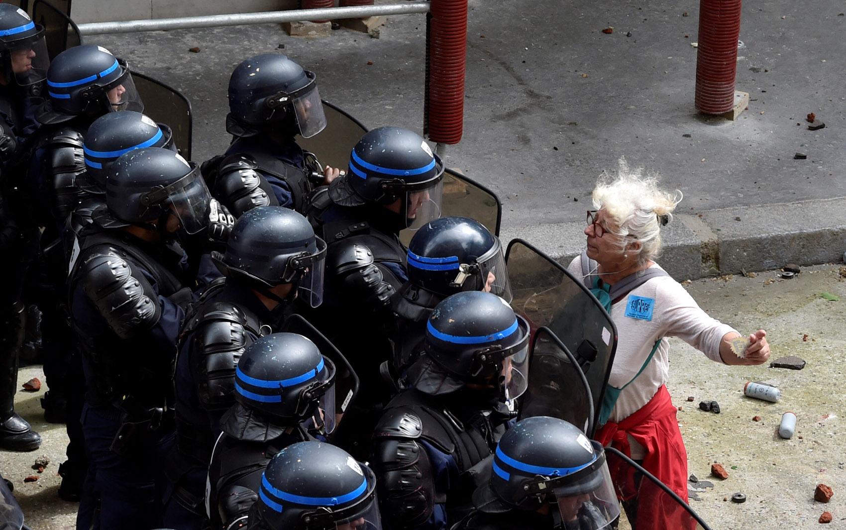 Uma mulher encara uma barreira de policiais durante protesto contra as reformas trabalhistas do governo em Paris, na França