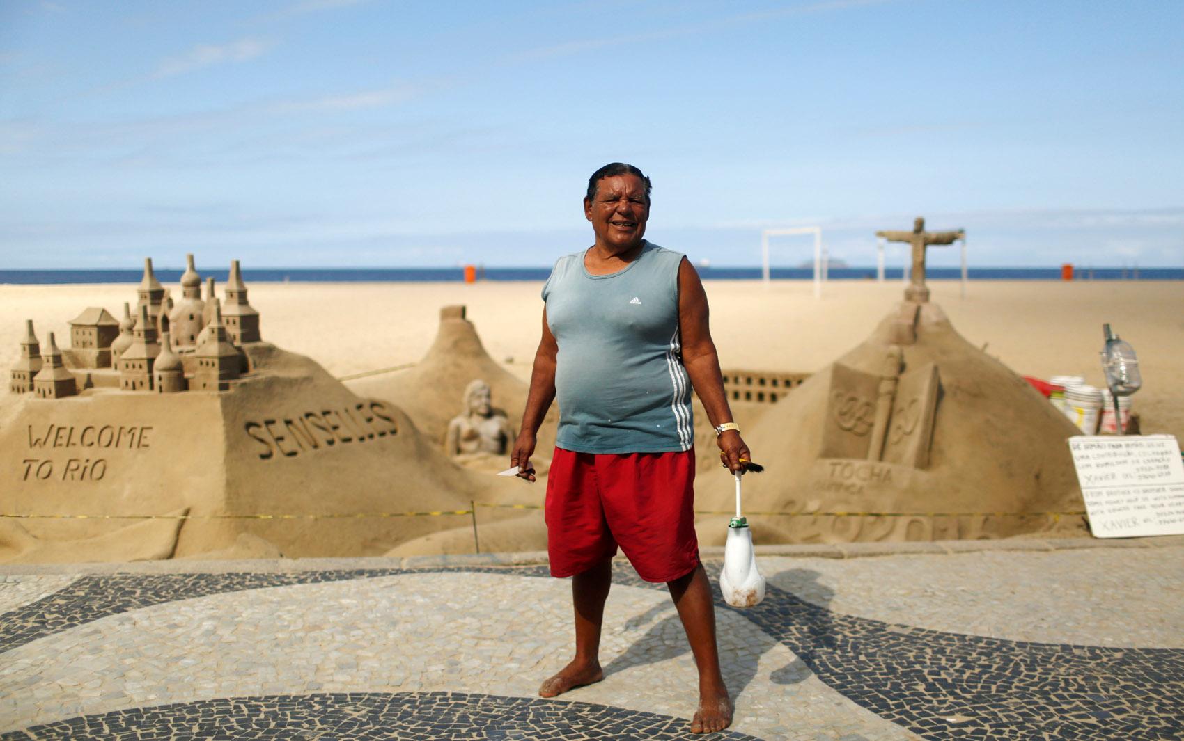 Xavier Fonseca, escultor de areia de 70 anos, posa na praia de Copacabana. Para ele 'Os jogos são uma grande oportunidade para as pessoas que trabalham com turismo'. Ele também acha que os cariocas vão se beneficiar das melhorias no transporte público
