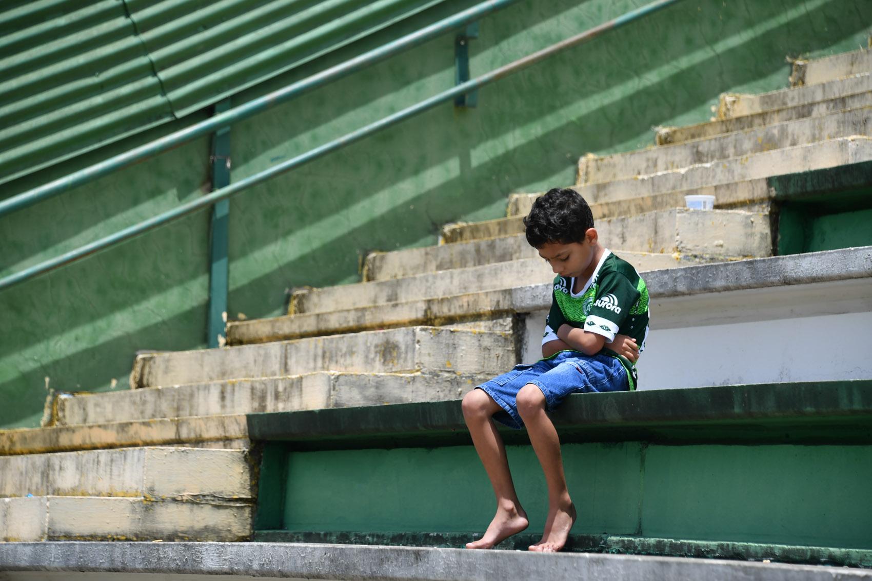 Resultado de imagem para Um menino se senta sozinho na arquibancada da arena Condá em Chapecó (SC)