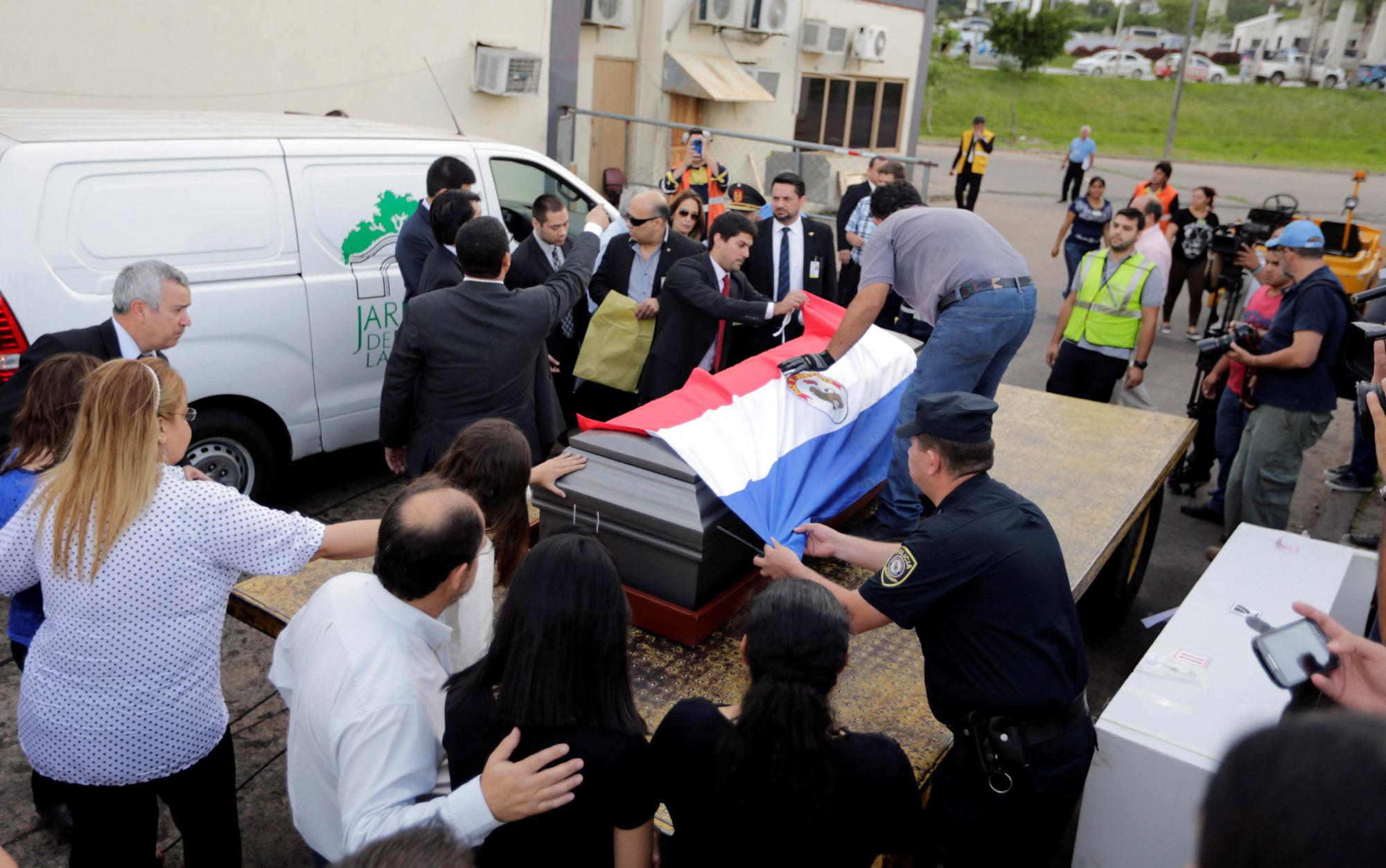 Familiares, amigos e vizinhos colocam uma bandeira do Paraguai sobre o caixão de Gustavo Encina, piloto paraguaio do avião da Chapecoense,  no aeroporto internacional Silvio Pettirossi em Luque, no Paraguai