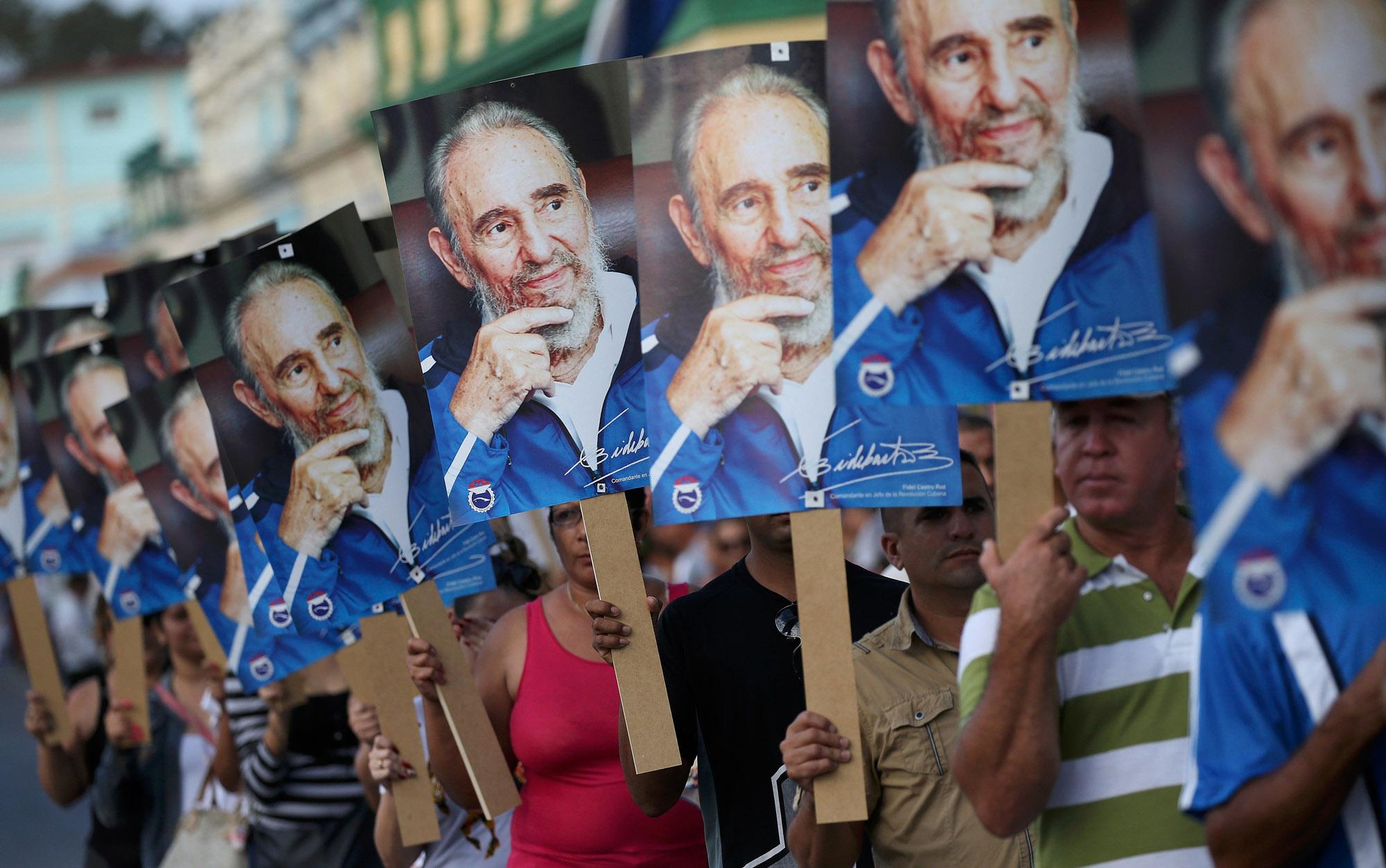 02/12 - Pessoas seguram fotos de Fidel Castro durante a chegada da caravana que percorre o país com as cinzas do ex-presidente cubano em Las Tunas