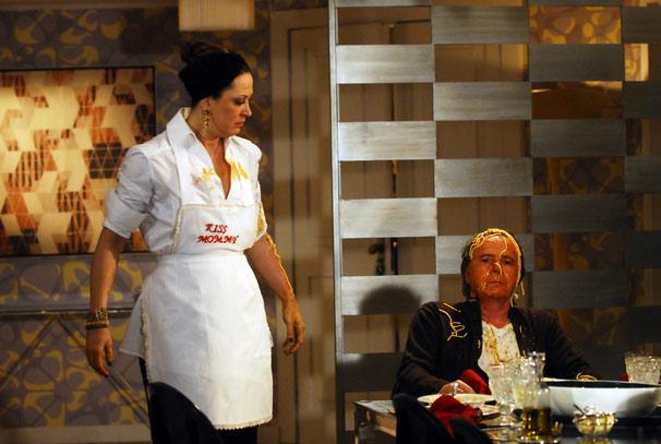 Jaqueline (Claudia Raia) joga uma travessa de macarrão na cabeça de Breno (Tato Gabus Mendes)