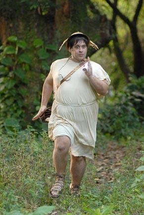 O mensageiro Jorginopoulos (Leandro Hassum) correndo na floresta para entregar a mensagem ao rei