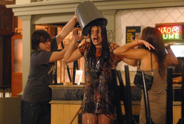 Lorelai (Luiza Casé) leva um balde d'água suja na cabeça