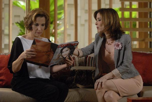 Eunice (Deborah Evelyn) mostra para Clarice (Ana Beatriz Nogueira) as fotos de Natalie Lamour (Deborah Secco) posando na revista com a imagem de Cortez ao fundo (Foto: TV Globo / Marcio Nunes)