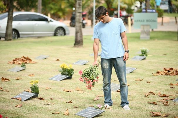 Pedro (Bruno Gissoni) deixa flores no túmulo da mãe de Raquel (Ariela Massoti)  (Foto: TV Globo/Marcio Nunes)