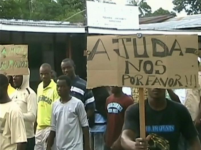 Estrangeiros caminharam com faixas e cartazes nas mãos (Foto: Jornal do Amazonas)