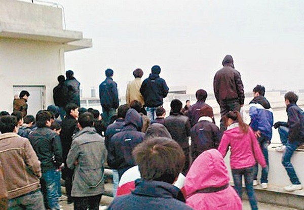 Funcionários da Foxconn ameaçam se jogar de um prédio (Foto: Reprodução/The Daily Chili)