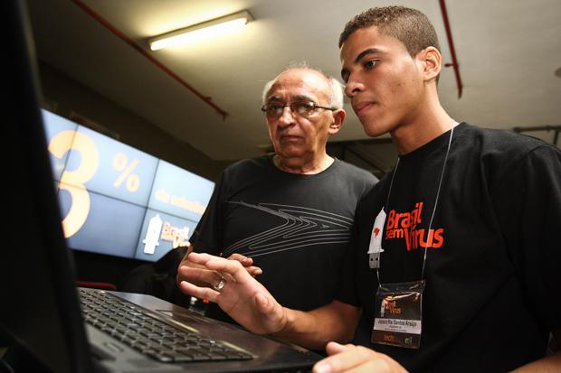 Morador recebe a orientação da equipe para aprender a vacinar o computador. (Foto: Brasil sem Vírus)
