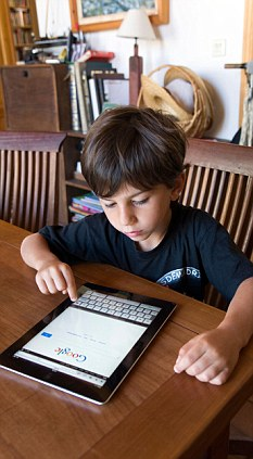 Child using Apple iPad 2 tablet computer at home
