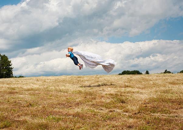 Henry, o bebe voador, filho da fotógrafa Rachel Hulin num campo com sua capa Foto Rachel Hulin
