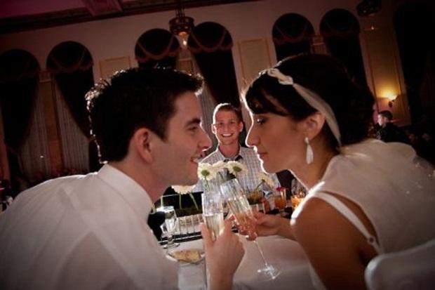 Homem sorrindo entre casal de noivos (Foto: Reprodução)