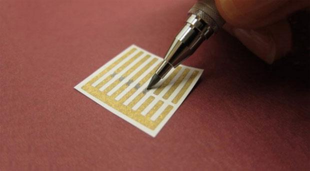 Na foto, lápis desenha conexões feitas de nanotubos de grafeno entre terminais de outo (Foto: Reprodução)