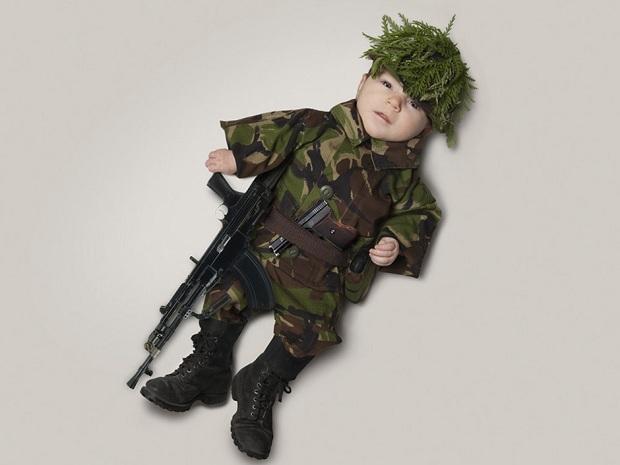 De farda e uma mini metralhadora, bebê faz ensaio de fotos com o pai (Foto: Reprodução/mondaymonday)