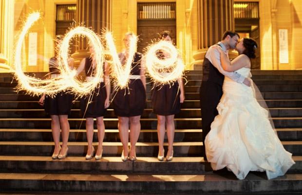 """Fotografia de casal ao lado das madrinhas escrevendo palavra """"love"""" com fogos de artifício (Foto: Mary Dougherty)"""