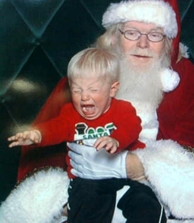 Menino tenta escapar dos braços de papai noel (Foto: Reprodução)