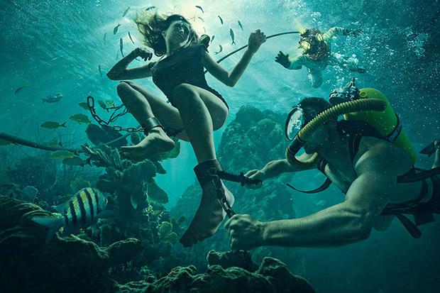 Imagem de uma mulher presa em corrente sendo libertada por mergulhador (Foto: Dave Hill)