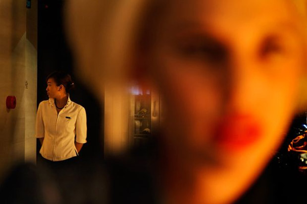 Imagem de mulher ao fundo em foco, à esquerda, e imagem de pessoa fora de foco, à direita (Foto: Randy Olson)