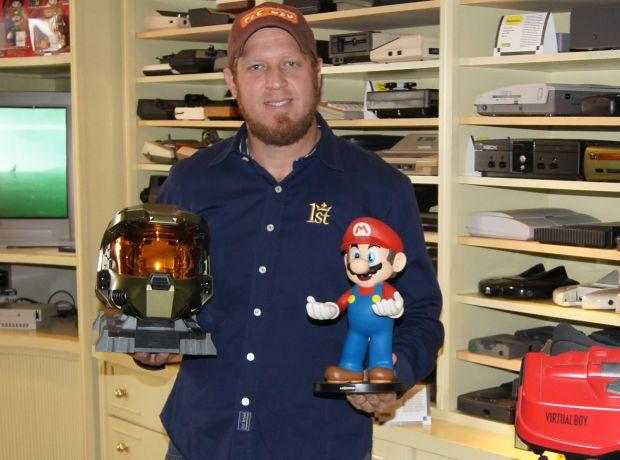 Alex Mamed com um capacete do herói Master Chief, de Halo, e um boneco de Mario, na frente de sua estante de consoles (Foto: Divulgação)