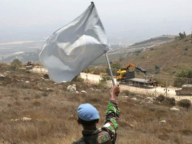 Funcionário da missão da ONU levanta bandeira em região de patrulha israelense na fronteira com o Líbano