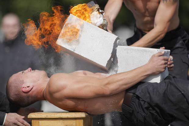 Soldado quebra bloco de concreto em chamas sobre o peito de colega.