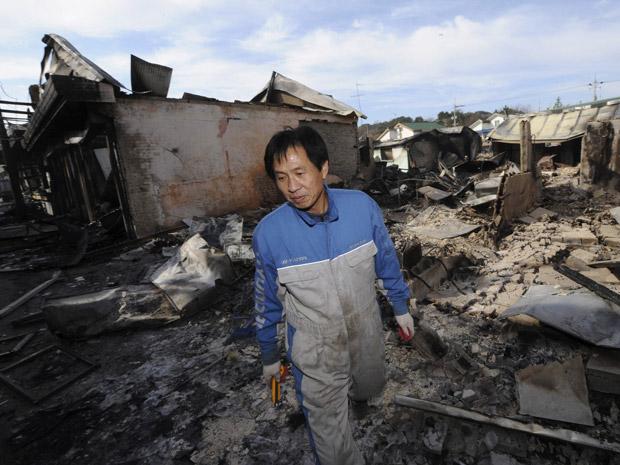Morador percorre nesta quarta-feira (24) área da ilha de Yeonpyeong destruída pelo ataque norte-coreano da véspera.