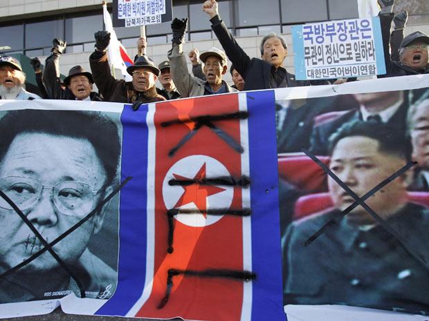 Manifestantes gritam contra o líder norte-coreano Kim Jong-il e seu filho, Kim Jong-un, em protesto na capital sul-coreana, Seul, nesta quinta-feira (25)
