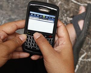 Usuário mexe em smartphone BlackBerry