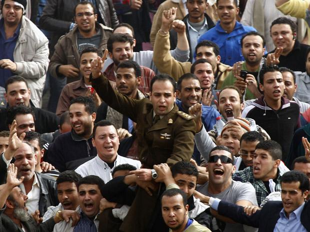 Oficial do exército se junta a manifestantes na praça Tahrir, durante protesto no Cairo
