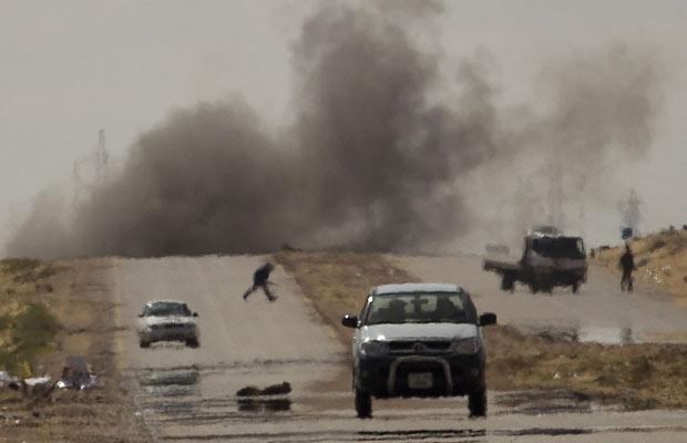 Opositores se protegem de bombardeio das forças de Kadhafi, na cidade de Ajdabiya (Foto: Anja Niedringhaus/AP)