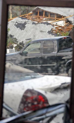 Vidro mostra imagem de destruição após o tornado da região de Clinton, no Mississipi (Foto: Rogelio V. Solis/AP)
