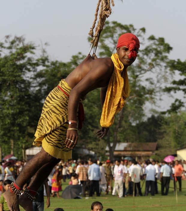Indiano fica suspenso por ganchos cravados em suas costa na quarta-feira (20) durante as celebrações do festival Rongali Bihu em Boko, na Índia. (Foto: Anupam Nath/AP)