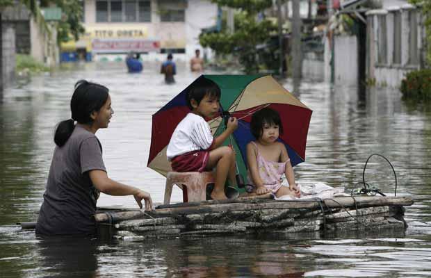 Moradora improvisa balsa para salvar crianças na cidade filipina de Dampalit nesta quarta-feira (28) (Foto: AP)