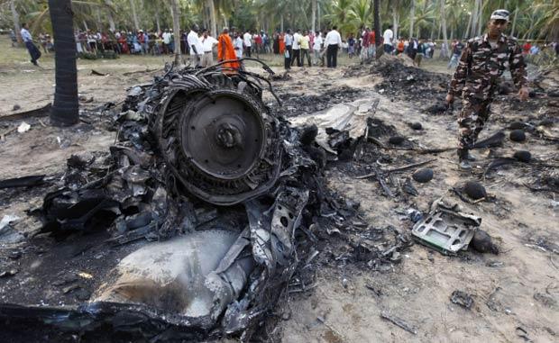 Moradores observam destroços de um MIG-27 russo que caiu em Marawila, a 60 quilômetros de Colombo, capital de Sri Lanka, na segunda-feira (13) (Foto: Reuters)