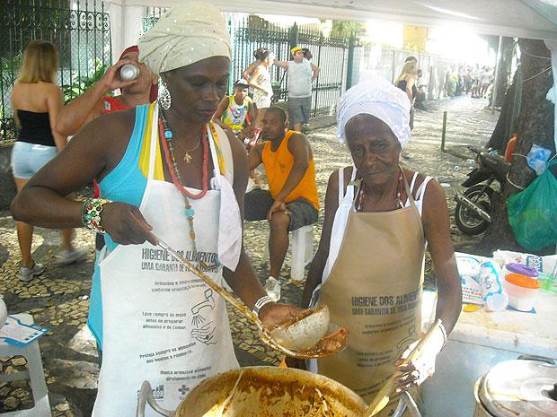 Dona Cleonice e a filha Crispina trabalham vendendo feijoada no circuito do carnaval em Salvador (Foto: Lílian Marques/ G1)
