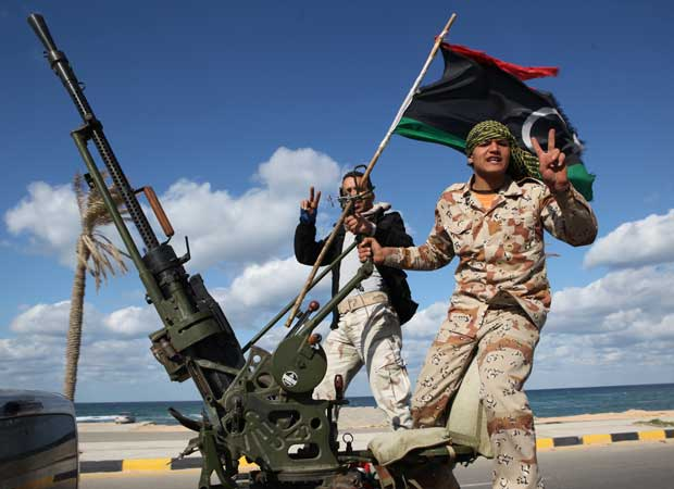 Ex-combatentes rebeldes líbios marcham em direção a Trípoli, capital do país, em 14 de fereveiro (Foto: AP)