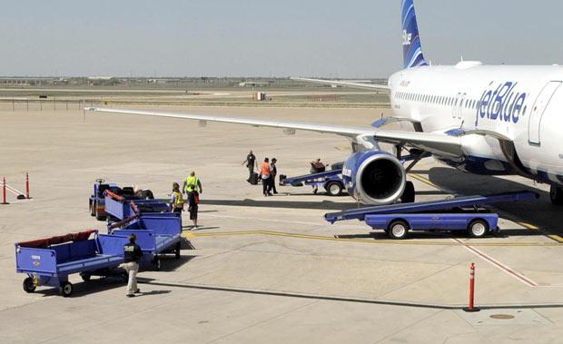Equipes de segurança vasculham o avião após o pouso inesperado em Amarillo, no Texas, nesta terça-feira (27) (Foto: AP)