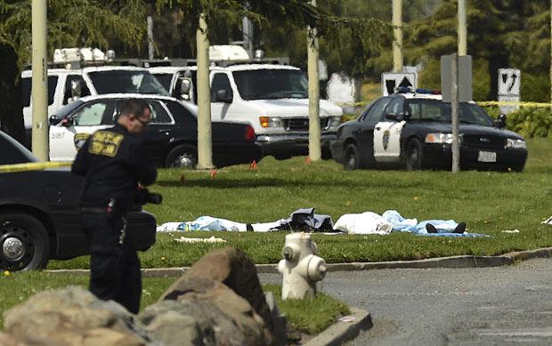 Corpos cobertos no gramado da escola Oikos University, em Oakland, na Califórnia, que foi invadida por atirador nesta segunda-feira (2) (Foto: Noah Berger / AP)
